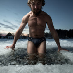 Young man having recreational swim in the ice hole
